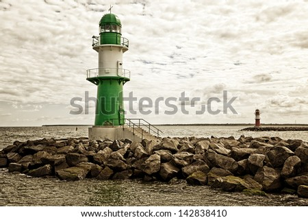 Green and red lighthouses at the harbor entrance of Rostock Warnemunde - stock photo
