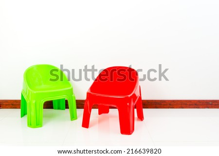 Green and red plastic chair with white wall - stock photo