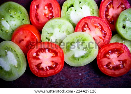 Green and red tomato over brown background - stock photo
