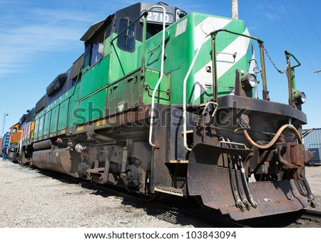 Green and weight freight train with blue sky background - stock photo