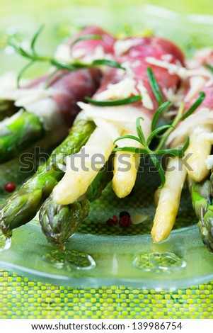 Green and white asparagus wrapped in prosciutto ham - stock photo
