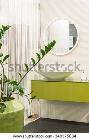 Green and white bathroom interior with sink and round shape mirror and