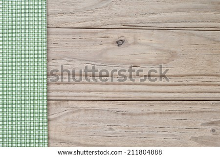 Green and white checkered tablecloth on wooden background - stock photo