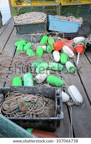 Green and white lobster bouys on the dock. - stock photo