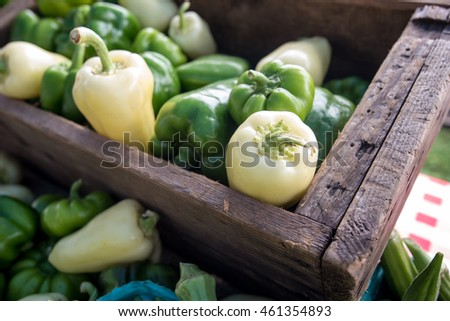Green and white peppers for sale at a farmers' market.