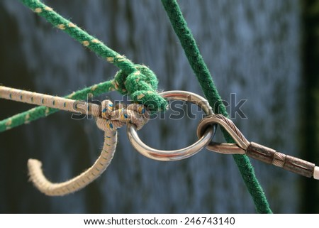 Green and white rope tied to a metal o-ring as found in a sailing boat rig as part of the mast and sail rigging, which can be read as a visual metaphor for teamwork or friendship - stock photo