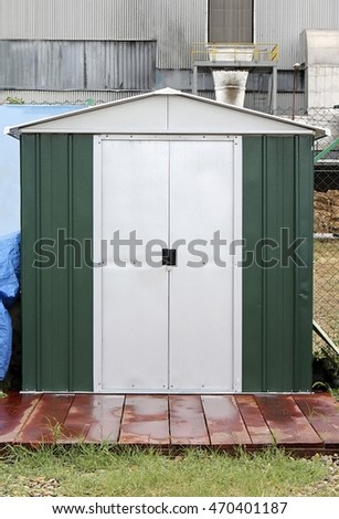 Green And White Storage Shed In Front Of Fabric