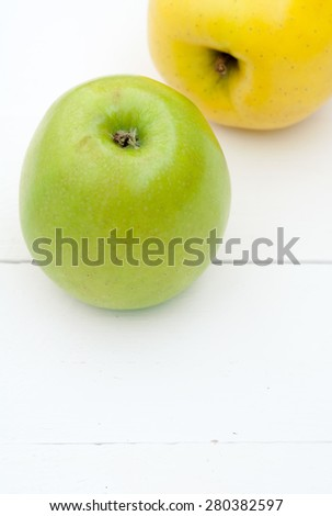 Green and yellow apples on a white wooden background closeup