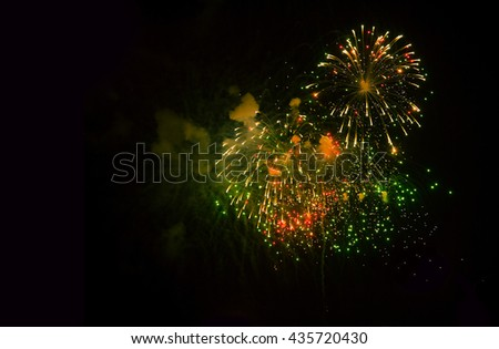 Green and yellow fireworks on black background, light show, copy space  - stock photo