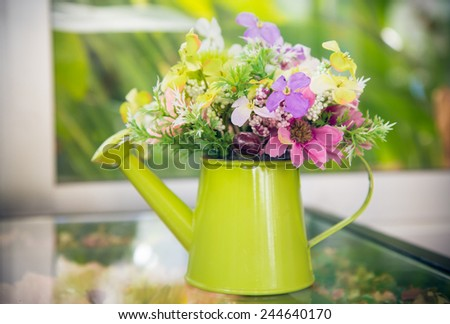 Green and yellow pitcher of peas with flowers on wooden table on window background
