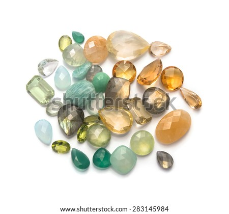Green and yellow shiny real gemstones isolated on white background. - stock photo