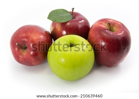 Green apple among red apples isolated on a white - stock photo