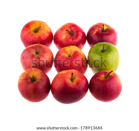 Green apple among red apples, isolated on white background. - stock photo