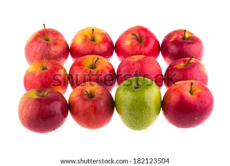 Green apple among red apples on white background. - stock photo