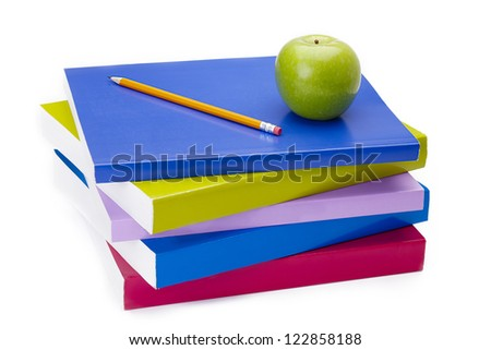Green apple and a sharpened pencil sitting on top of a stack of colorful books. - stock photo