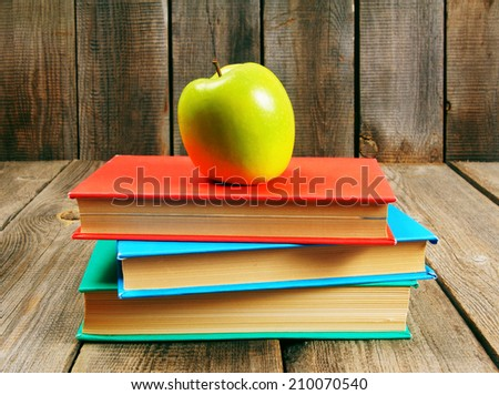 Green apple and books. On a wooden background. - stock photo