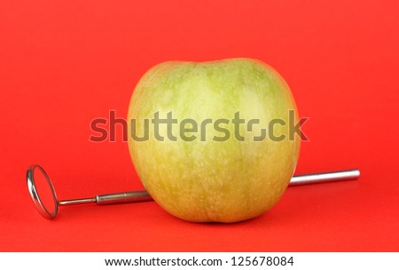Green apple and dental tool on color background - stock photo