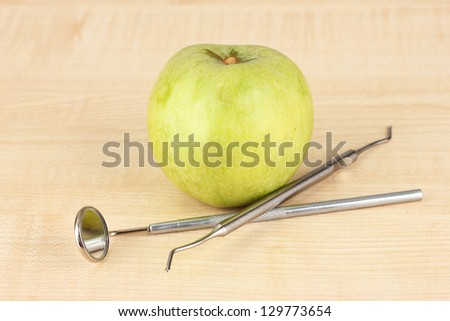 Green apple and dental tools on wooden background - stock photo