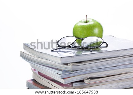 green apple and glasses on magazine and  book stack - stock photo