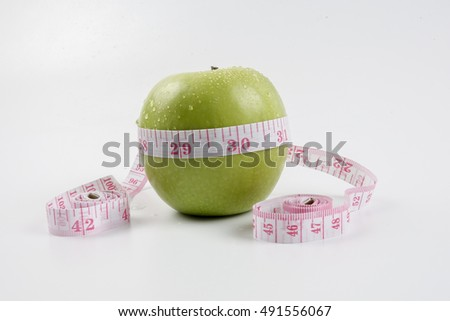 Green apple and measuring tape. Diet concept and copy space
