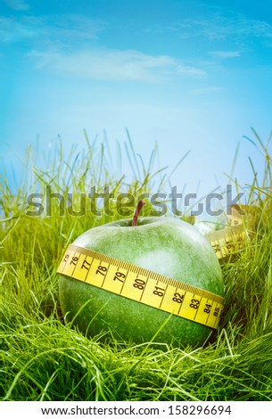 Green apple and measuring tape on the green grass. - stock photo