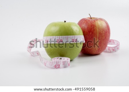 Green apple and red apple and measuring tape. Diet concept