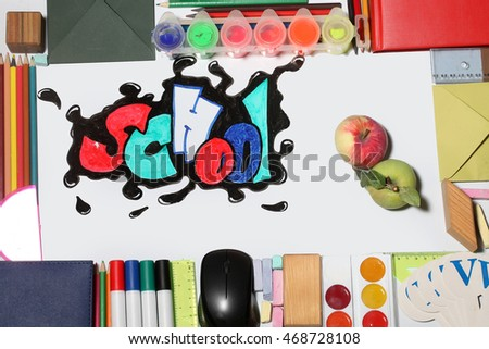 green apple and school text word painted graffiti with smiley eyes on paper near pencils markers computer mouse chalk ruler paint palette wooden cube notebook and alphabet on white background