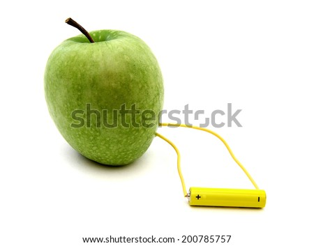 Green apple connected to a battery isolated over white background
