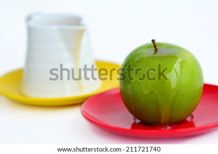 Green apple coverd in honey next to honey pot on Rosh Hashanah Jewish holiday.White background with copy space - stock photo