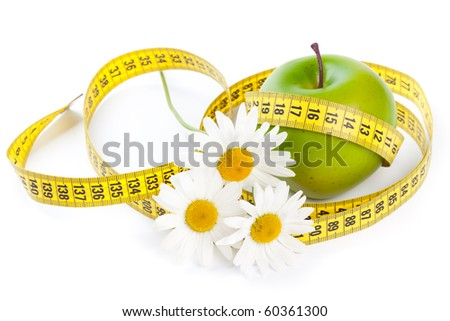 Green apple, flowers and measuring tape. Concept of healthy food. - stock photo