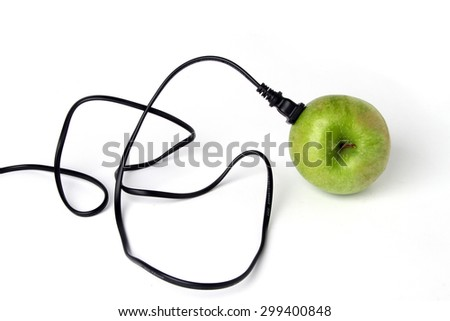 green apple - green energy - Black electric cable stab in fresh green apple