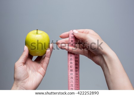 Green apple in female hands on gray background. Weight loss, diet - stock photo