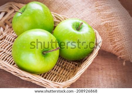 Green apple in wicker basket - stock photo