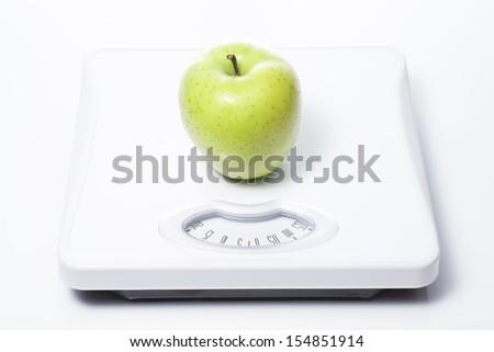 Green apple on Bathroom scale - stock photo