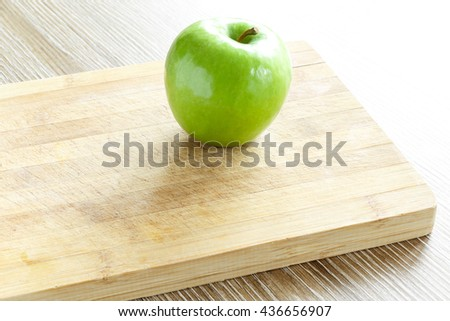 Green apple on cutting board