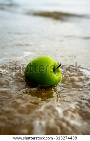 Green apple on the beach at sunrise .