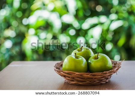 green apple on the table outside the home with natural light. according to the concept of freshness, health food and drinks or restaurants, supermarkets, green apple based products. - stock photo