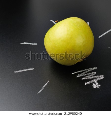 Green apple over the glowing bulb drawn on the blackboard as a back to school composition - stock photo