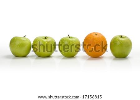 Green apple row with an orange toward the right - stock photo
