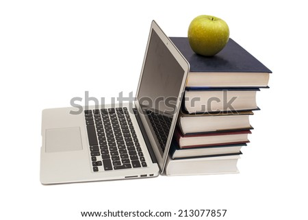 Green apple sitting on top of computer and books