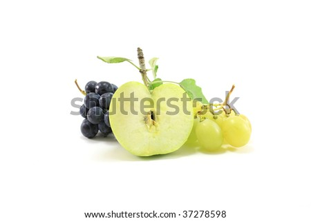Green apple slice with leaves and white and black grape