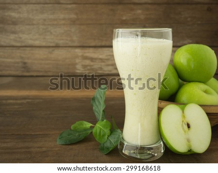 green apple smoothie in glass on wooden background - stock photo