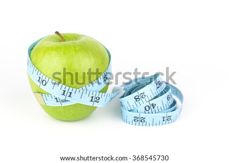 green apple surrounded by blue measurement tape on white background