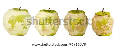 Green apple with a carving of the world map shown four times over a timespan of its deterioration. - stock photo