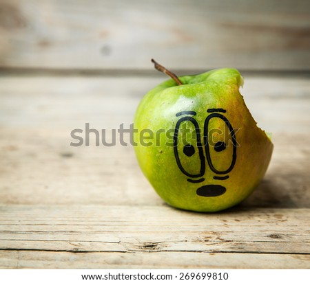 green apple with a hole bitten into it on a brown wooden surface - stock photo