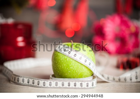Green Apple with a measuring meter and Christmas decorations - stock photo