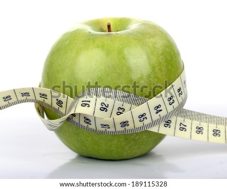 Green apple with a tape measure  Green apple wrapped in a tailor's tape measure on a white background .