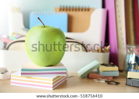 Green apple with colorful stationery
