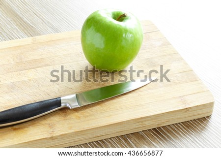 Green apple with knife on cutting board