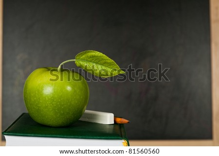 Green apple with leaf against blackboard in class. School concept - stock photo
